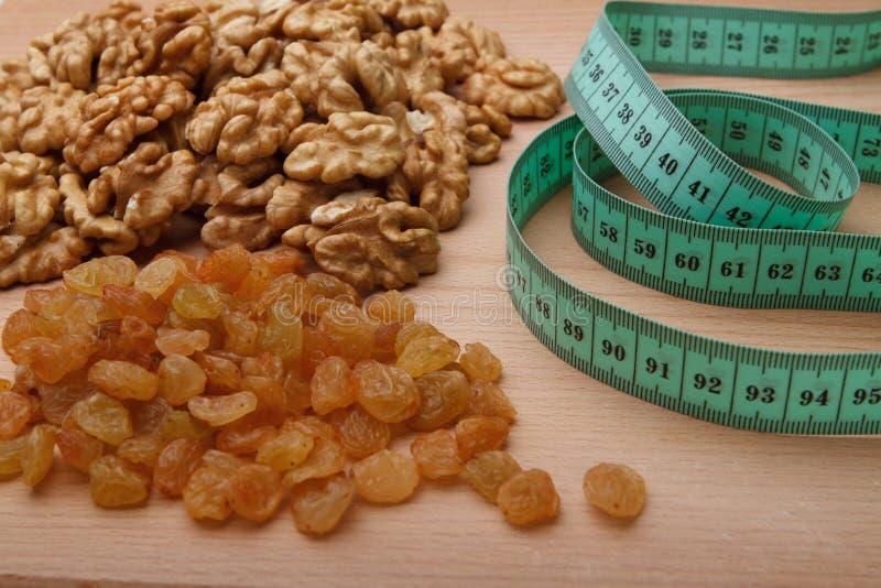 Walnuts, raisin and tape measure stock photography
