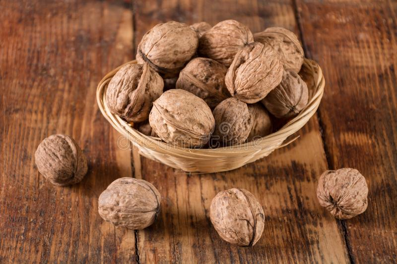 Walnuts in retro bowl and spilled on wooden desk. Raw beautiful natural walnuts in retro bowl and spilled on wooden desk. Autumn food concept. Close up stock images