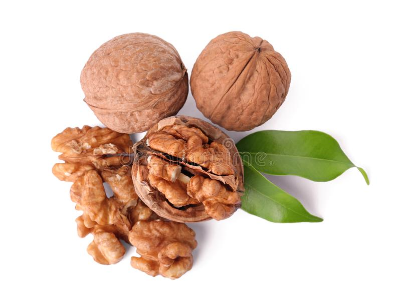 Walnuts in shell, kernels and green leaves. On white background, top view royalty free stock photos