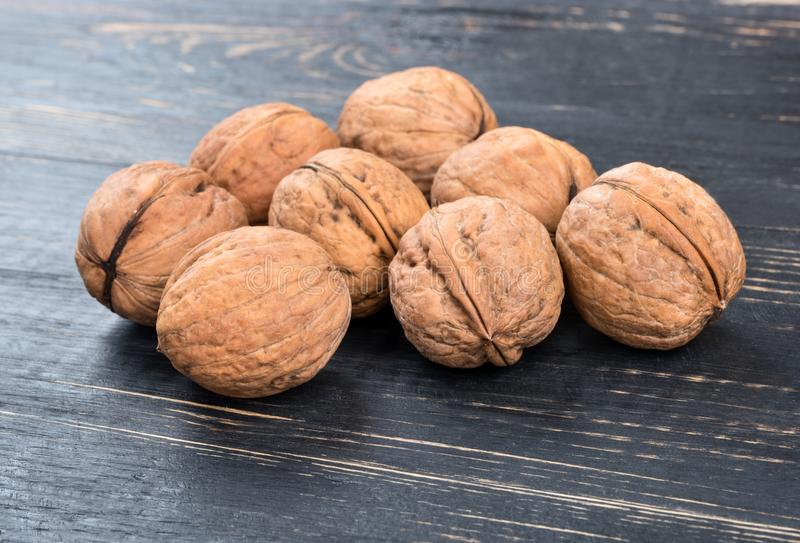 Walnuts on table. Several inshell walnuts on a dark table closeup stock image