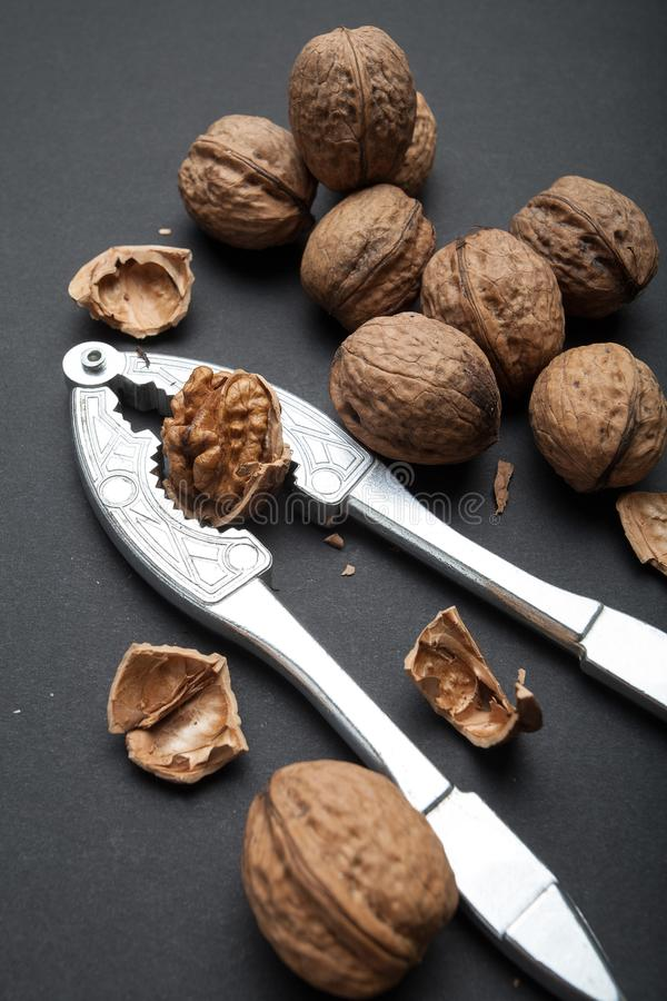 Walnuts and tongs for breaking on a black background.  stock photo