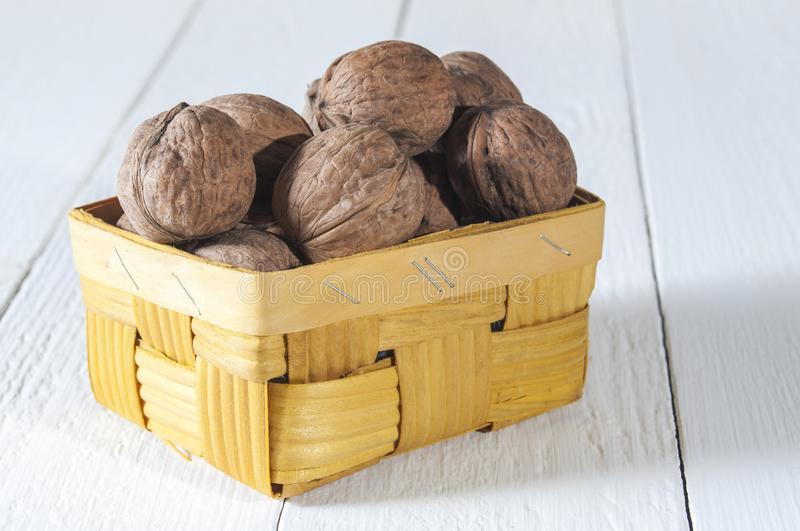 Walnuts in wicker basket on white wooden table. Healthy food and health care royalty free stock photo