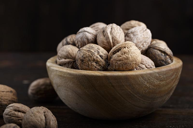 Walnuts on a wooden background. Inshell whole walnuts on dark wooden background. in a wooden plate royalty free stock photos