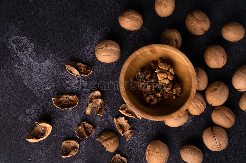 Walnuts in wooden bowl and on black slate surface. Healthy nuts and seeds composition. stock images