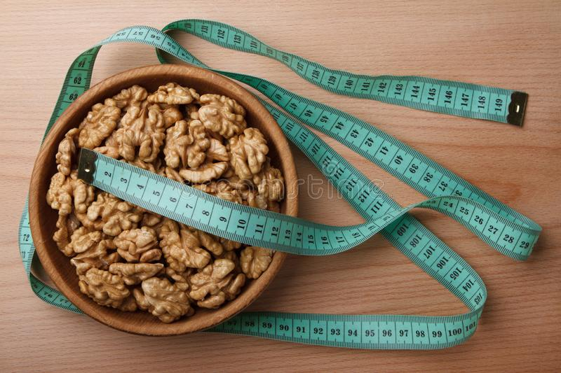 Walnuts in wooden bowl and type measure stock photography