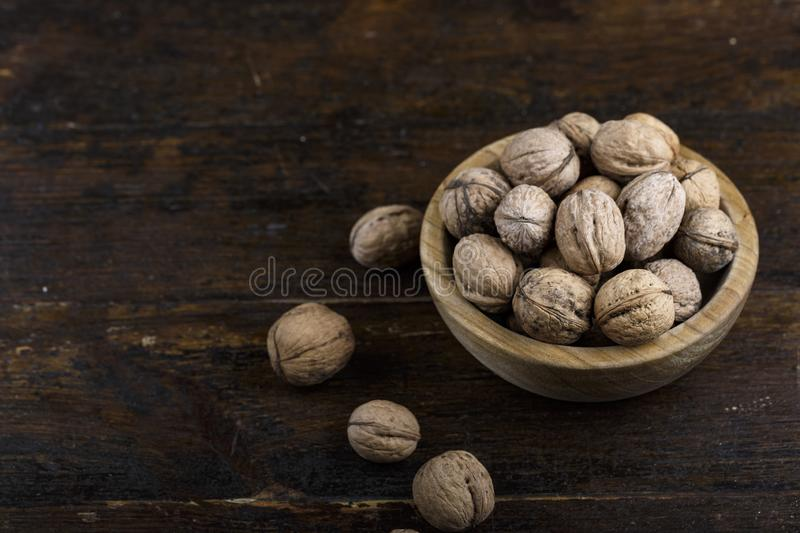 Walnuts in a wooden plate. Inshell whole walnuts on dark wooden background. in a wooden plate royalty free stock image