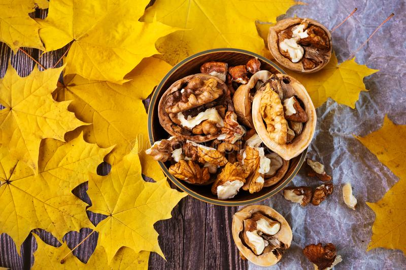 Walnuts in a wooden plate, next to them are yellowed maple leaves. Wooden and paper background. Autumn beautiful background, top view stock photo