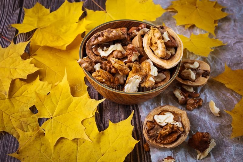 Walnuts in a wooden plate, next to them are yellowed maple leaves. Wooden and paper background. Autumn beautiful background, top view stock image