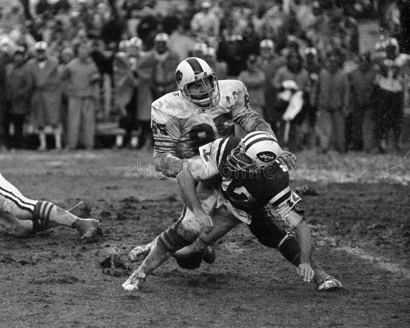 Walt Patulski. Buffalo Bills DL Walt Patulski knocks Jets QB Joe Namath to the ground. (Image taken from a B&W negative royalty free stock photos