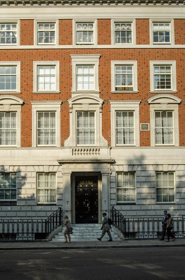 Walter Hines Page home, Grosvenor Square. LONDON, UK - JULY 25, 2017: Office workers walking home past the imposing office and apartment block in Grosvenor royalty free stock image