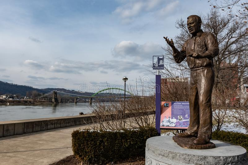 Walter Reuther statue with bridges in background. Wheeling, West Virginia/USA-March 7, 2019: Memorial statue of Walter Reuther with the Suspension Bridge in the stock photos