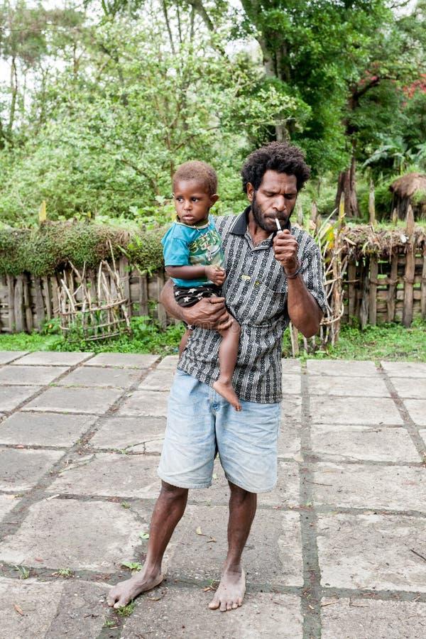 Wamena, Indon?sia - 9 de janeiro de 2010: Homem com a crian?a do tribo de Dani em uma posi??o usual da roupa em Dugum Dani Villag foto de stock royalty free