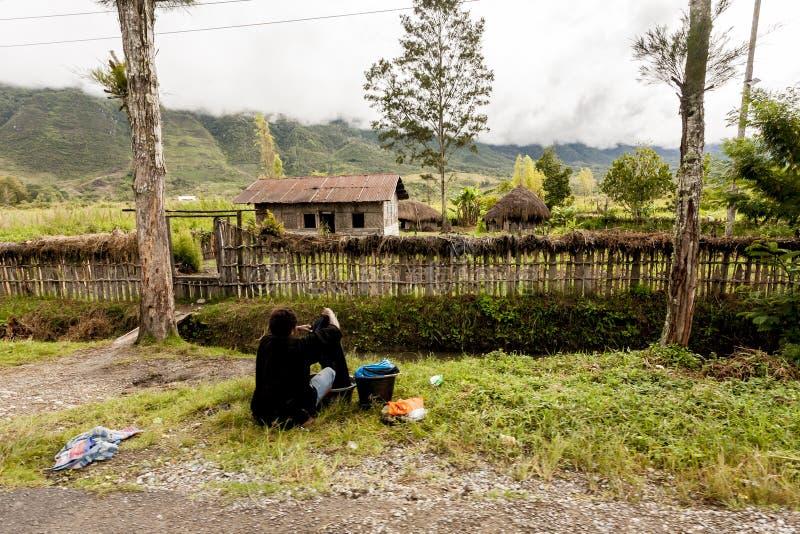 Wamena, Indonesia - 9 gennaio 2010: Donna di Dani che lava i vestiti su una strada rurale nella valle di Baliem, Papuasia Nuova G immagine stock libera da diritti