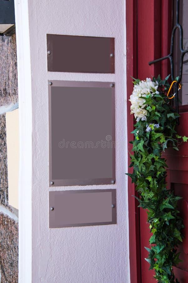 Wand auf der Seite eines Einganges mit einer roten Tür Es gibt leere drei silberne Zeichen auf der Wand stockfoto