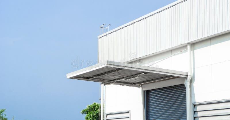 Wand-, Dach- und Fensterladentür der Fabrik oder des Lagergebäudes im Industriegebiet mit Raum des blauen Himmels und der Kopie stockfotografie