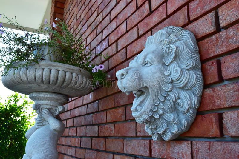 Wand des roten Backsteins mit Lion Face Sculpture lizenzfreie stockfotos