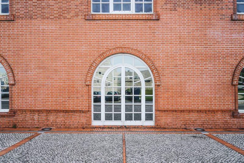 Wand des roten Backsteins mit schönem weißem Bogenfenster Detail des Gebäudes mit typischer europäischer Architektur lizenzfreie stockfotografie