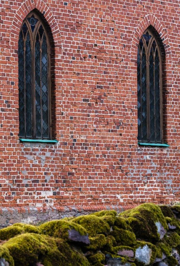 Wand des roten Backsteins mit zwei vertikalen Fenstern stockfotos