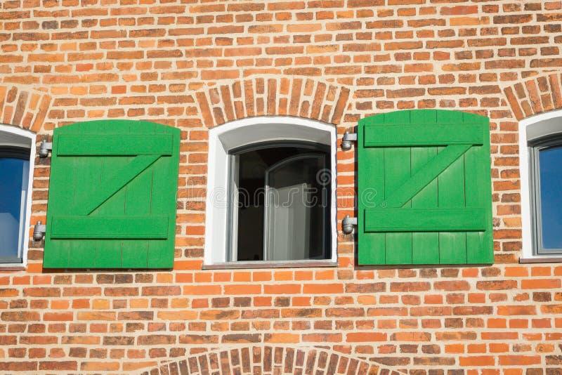 Wand des Weinleseroten backsteins und offenes Fenster mit grünen hölzernen Fensterläden stockbild