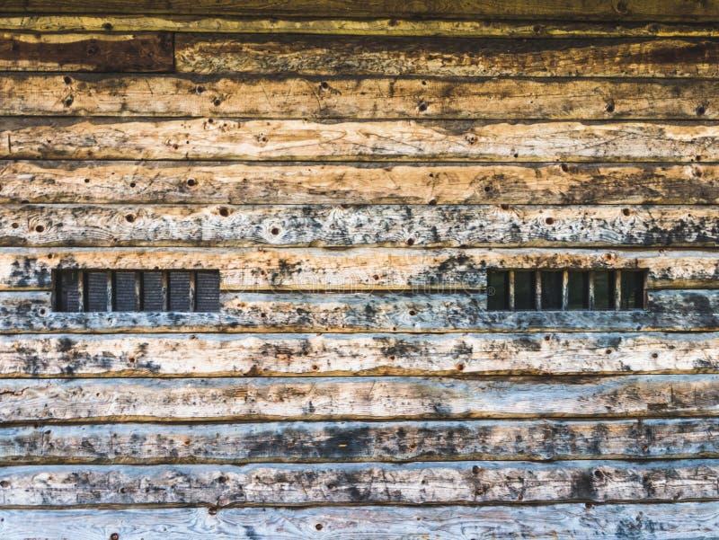Wand einer hölzernen Scheune mit Fenstern stockfoto