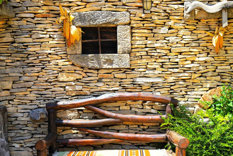 Wand eines ländlichen Herbsthauses mit einem kleinen Fenster, eine Holzbank Dorfhaus im Laubfall stockfotografie