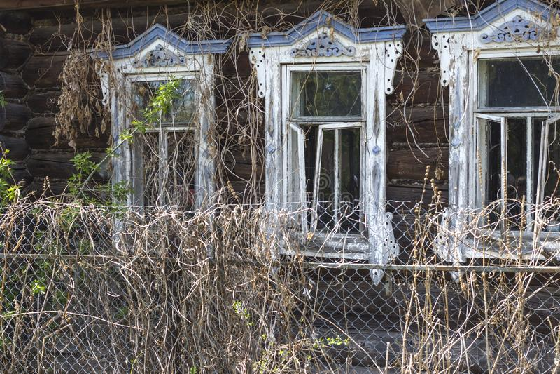 Wand mit Fenstern eines alten Holzhauses Verlassenes zerstörtes Holzhaus stockbilder