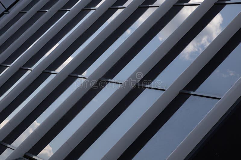 Wand mit Glasfenstern, die den blauen Himmel bei Tageslicht reflektieren stockbilder