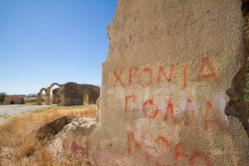 Wand mit Graffiti und Ruinen gotischer Kirche Heilig-Mütter im Hintergrund im verlassenen Dorf von Agios Sozomenos, Zypern lizenzfreie stockfotos