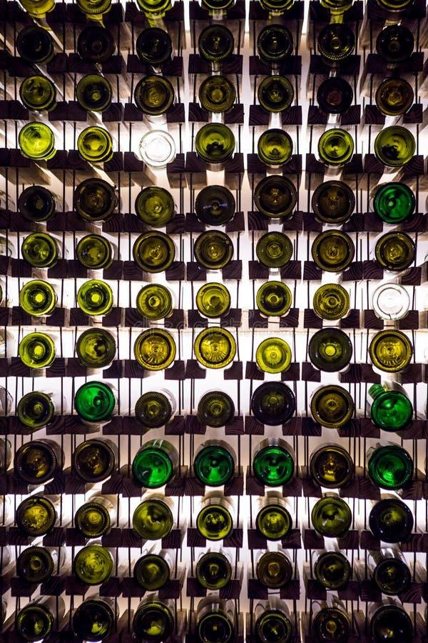 Wand von leeren Weinflaschen Die leeren Weinflaschen, die auf gegenseitig im Muster gestapeltwurden, beleuchteten durch das Licht lizenzfreies stockbild