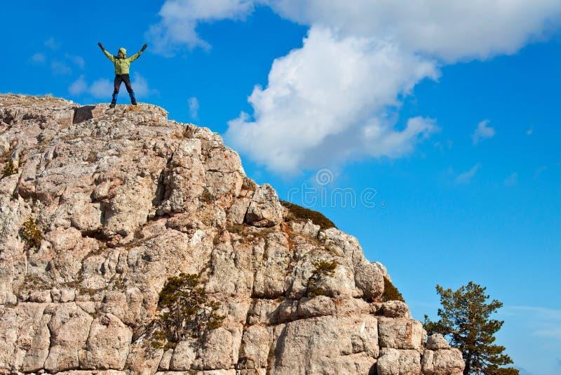 Wandelaar bij de bovenkant van een rots stock foto's