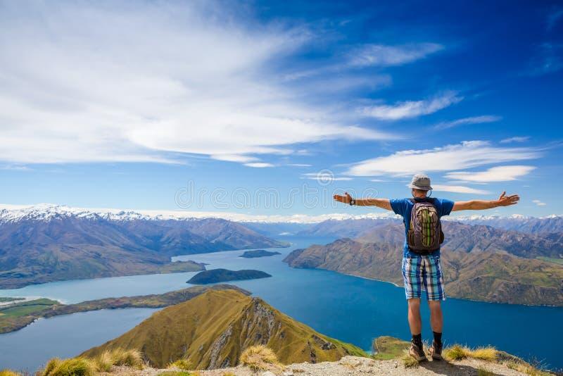 Wandelaar bij de bovenkant van een rots met zijn opgeheven handen stock afbeeldingen