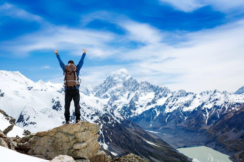 Wandelaar bij de bovenkant van een rots met zijn opgeheven handen stock foto