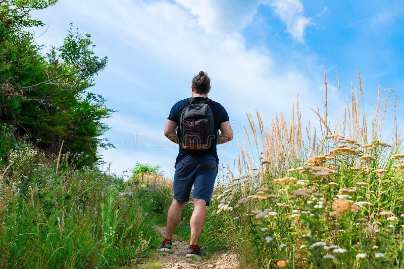 Wandelaar in blauwe borrels die zich op de bergsleep, bijna bij de bovenkant, met rugzak op zijn die rug bevinden, met groen gras stock foto's