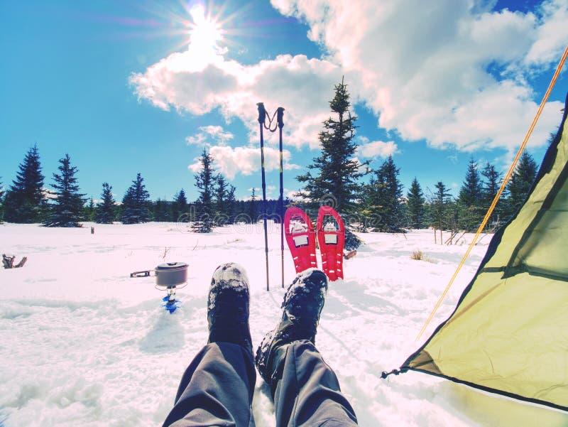 Wandelaar die in de winterbergen kamperen Mensen kokend voedsel met draagbaar gaskooktoestel stock foto