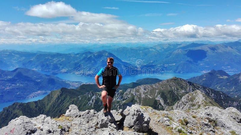 Wandelaar die in fronto van het panorama van het meer van Como glimlachen en stock afbeelding