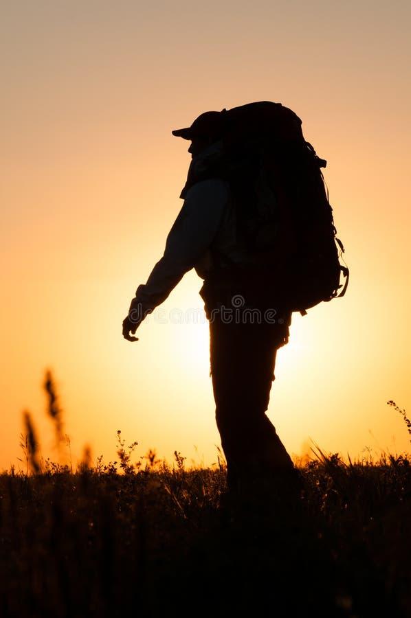 Wandelaar die met rugzak op het gebied lopen stock foto
