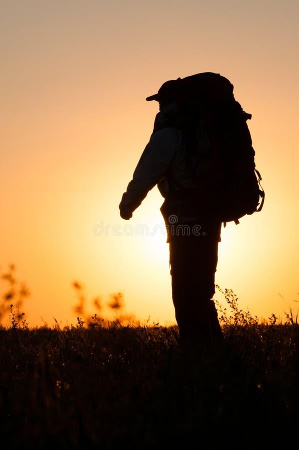 Wandelaar die met rugzak op het gebied lopen stock fotografie