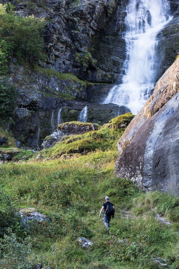 Wandelaar die met rugzak wandelen die waterval in park in het mooie landschap van de de herfstaard bekijken Portret van mannelijk stock fotografie