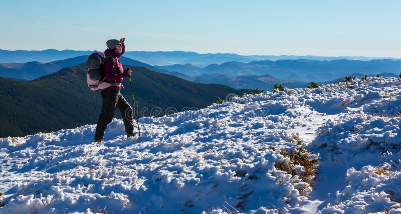 Wandelaar die op de Sneeuw Dragende Rugzak van de Berghelling naar boven gaan royalty-vrije stock fotografie