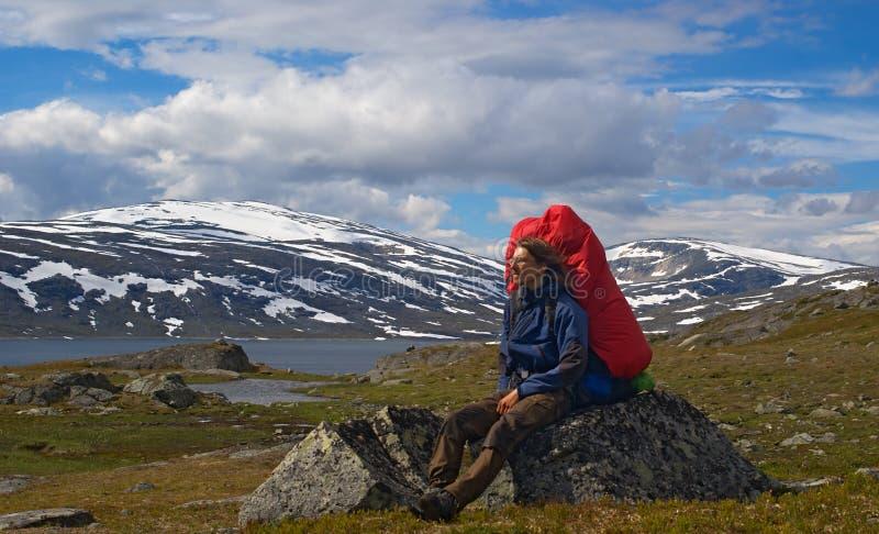 Wandelaar die op Rots rust stock foto