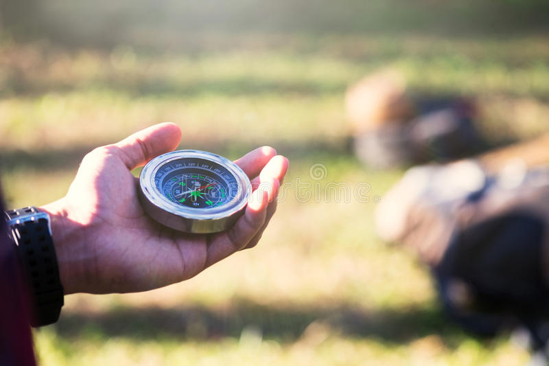 Wandelaar die richting met een kompas zoeken in het bos stock foto