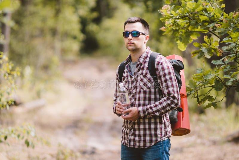 Wandelaar Drinkwater in Forest Tired-mensen drinkwater van fles in bos Knappe Reiziger met binnen Rugzak en Fles stock fotografie
