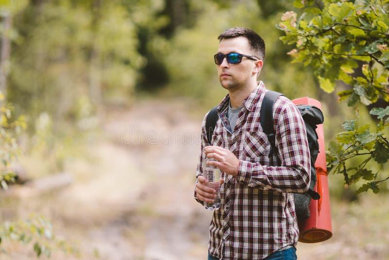 Wandelaar Drinkwater in Forest Tired-mensen drinkwater van fles in bos Knappe Reiziger met binnen Rugzak en Fles stock foto