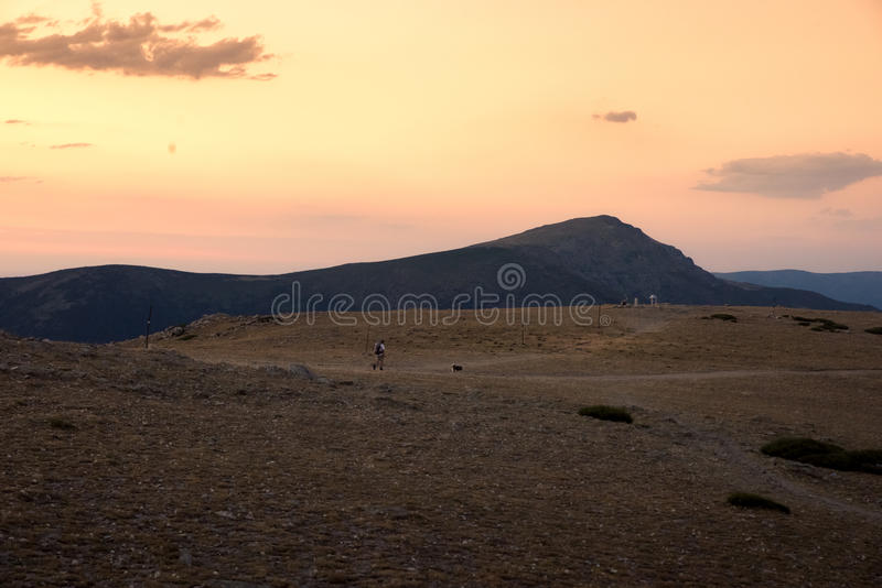 Wandelaar en zijn hondgang onderaan de berg in een verbazende zonsondergang stock foto's