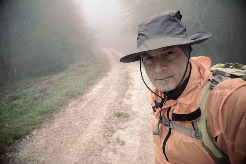 Wandelaar met Hoed die een Selfie langs Misty Path nemen royalty-vrije stock fotografie