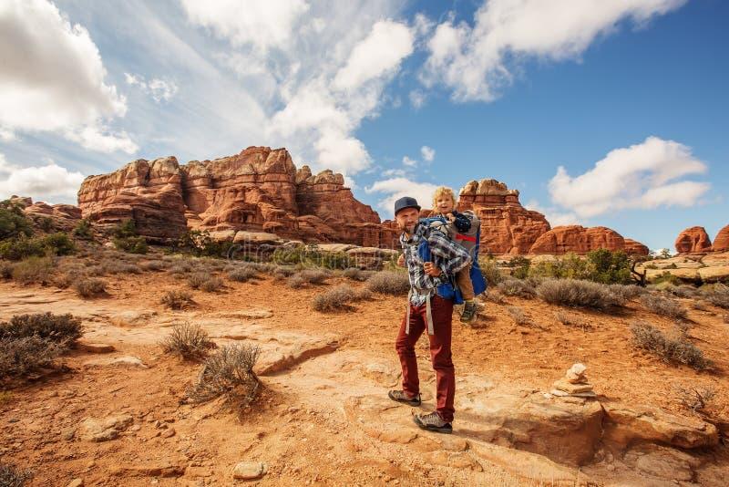 Wandelaar met jongen in het Nationale park van Canyonlands, naalden in de hemel, in Utah, de V.S. royalty-vrije stock afbeelding