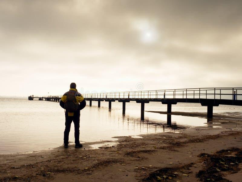 Wandelaar met rugzak alleen op zandig strand, zonsopgang boven overzeese brug royalty-vrije stock foto