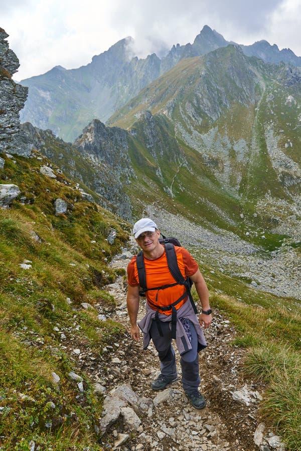 Wandelaar met rugzak in de bergen stock afbeelding