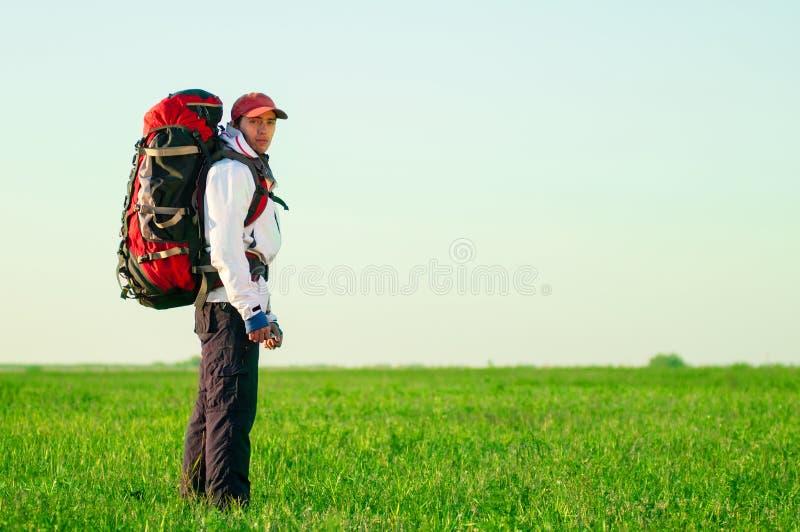 Wandelaar met rugzak die zich op het gebied bevinden stock foto