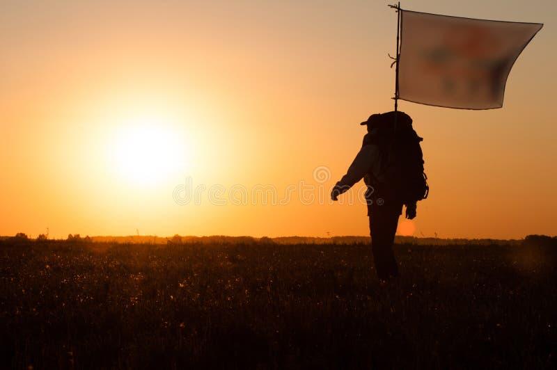 Wandelaar met rugzak en vlag die op het gebied lopen royalty-vrije stock afbeeldingen